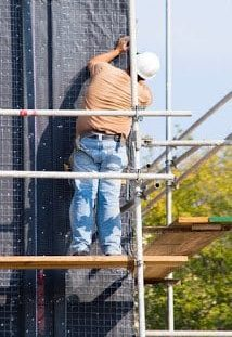 Worker working on scaffolding that follows the requirements set in ANSI/ASSE A10.8