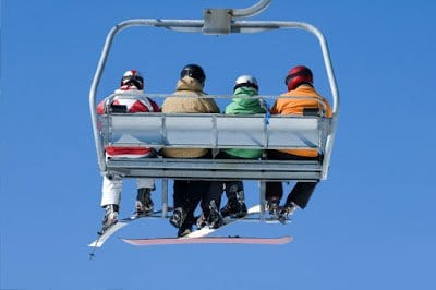 Four people siting on a ski chair lift