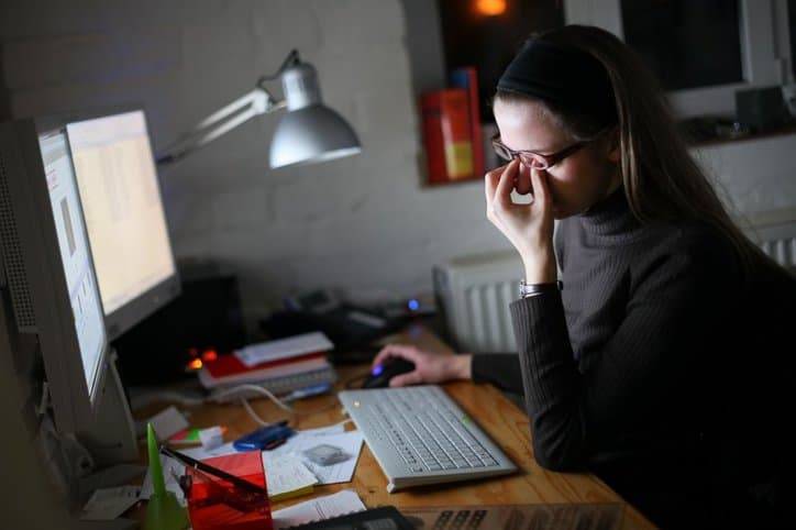 Woman struggling with Computer Vision Syndrome from repetitive stress.