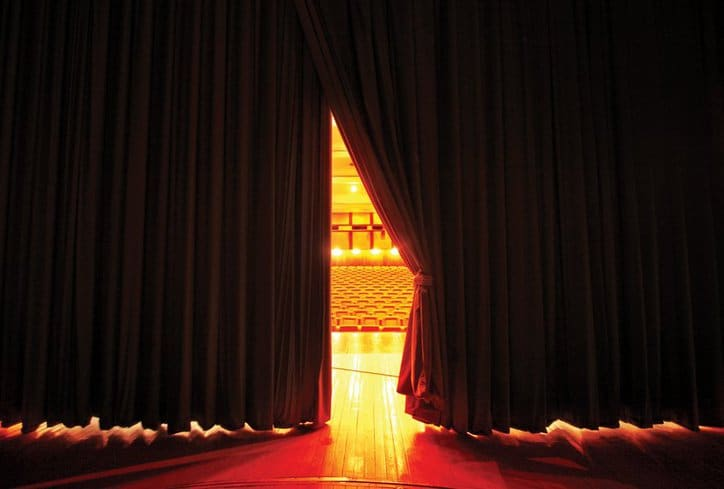 Curtain sliding open on stage, placing the star in the limelight.