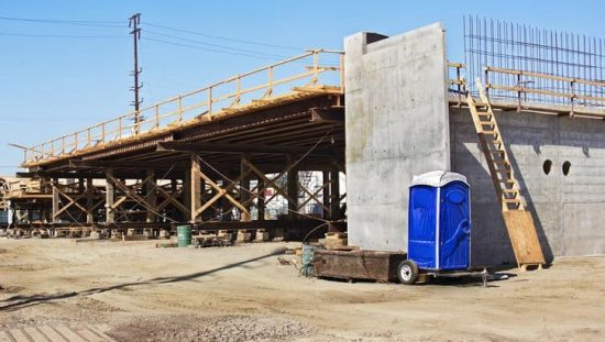 A blue porta potty as construction site bathroom adhering to ANSI Z4.3