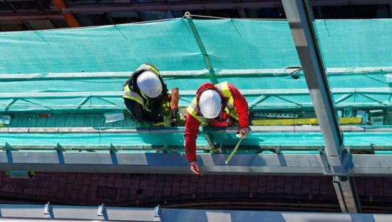 Two construction workers who are protected by ANSI/ASSE Z359 on the side of a building