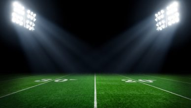 A verdant football field illuminating via IES RP-6-15 sports and recreational area lighting.