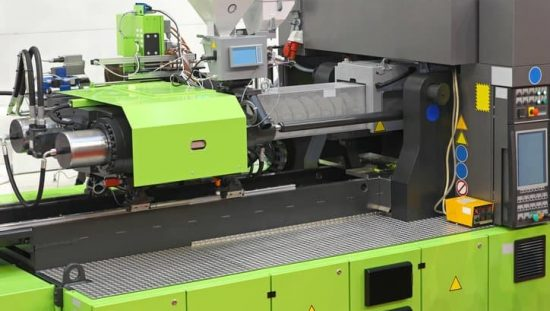 A green ANSI/PLASTICS B151.1-2017 injection molding machine