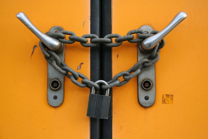 Door handles with a chain link around them and a lock on connecting the ends