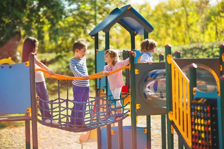 Children having specified fun on a safe ASTM F1487-21 public playground.