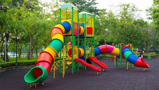 Colorful children's public playground kept safe with ASTM F1487-17