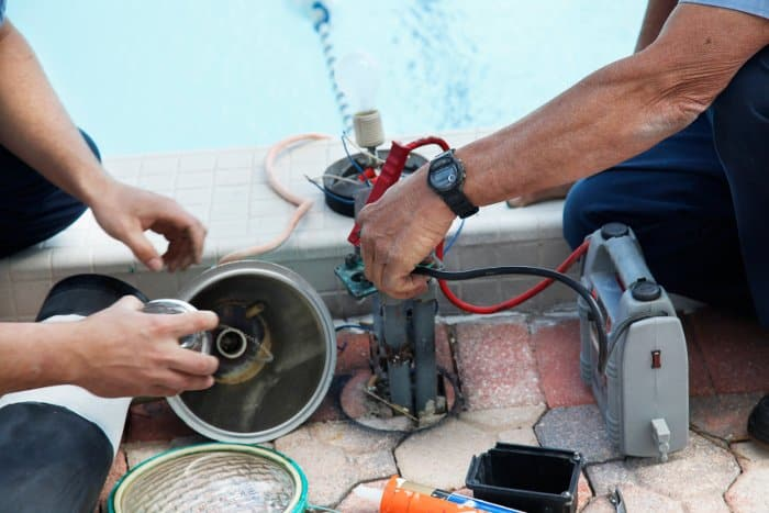 Workers putting together wires and electronic equipment beside swimming pool via NFPA 70 requirements.