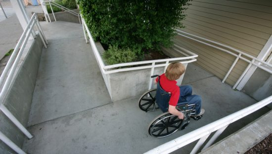 Young boy in wheelchair using ANSI A117.1-2017 ramp