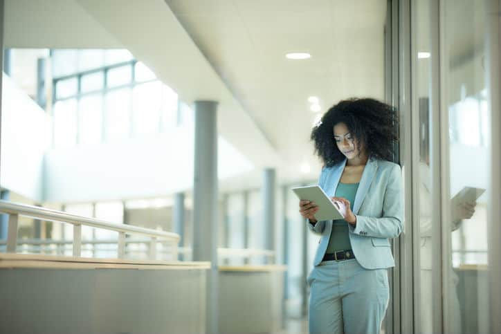 Woman in suit working on a tablet while following ISO/TS 9002:2016