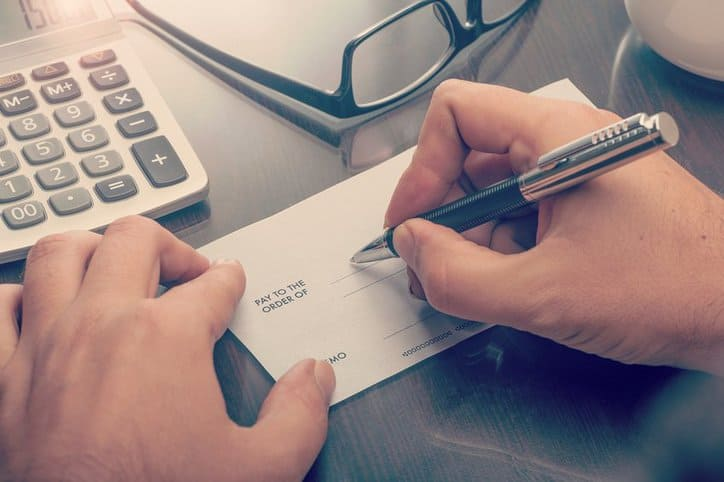 Hands using a pen to sign a check that needs to be reviewed by forensic document experts for fraud.