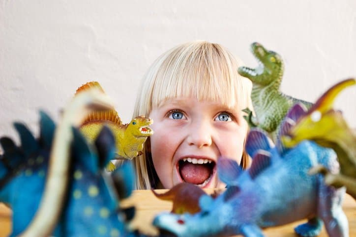 Happy child surrounded by toy dinosaurs that follow guidelines set by ASTM F963-17