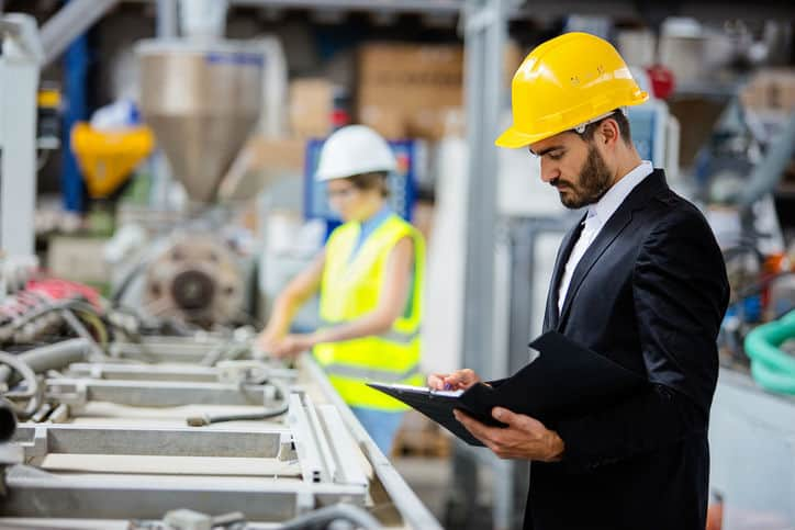 Man in suit looking at a clipboard while in a factory and following ISO/TS 9002:2016