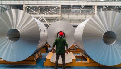 Man gazing in amazement at aluminum cylinders that follow aluminium standards.