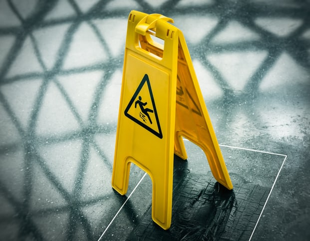 A yellow anti-slip caution sign is easily seen from its ANSI Z535 symbol.