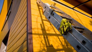 A portable metal ladders certified to ANSI ASC A14.2-2017 leaning against yellow house