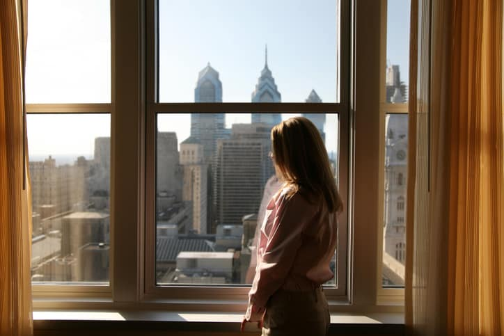 Woman gazing out window at Philadelphia skyline where many follow the North American Fenestration Standard.