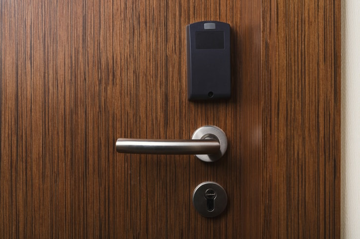 At a hotel, a brown door contains a secure ANSI/BHMA A156.23-2017 electromagnetic lock to lead into room.