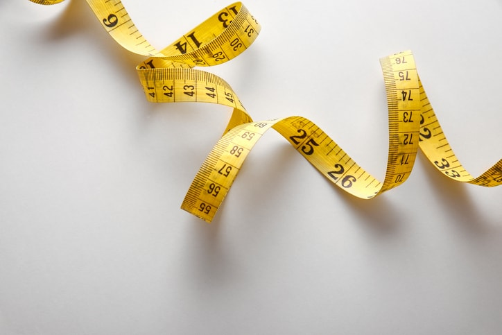 Twisting measuring tape representing the metric system (SI units), which are reflected in standards by an M.