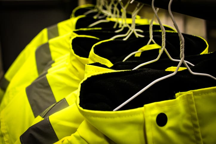 Line of yellow HVSA protective suits hung up to show what ISO 45001 does not cover for OH&S management systems.