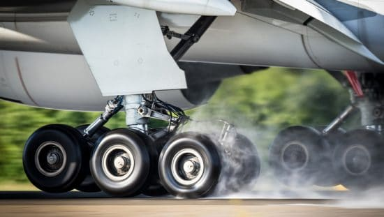 An aircraft landing to rubber burn and smoke, but it's secure thanks to SAE AMS 2430 shot peening.