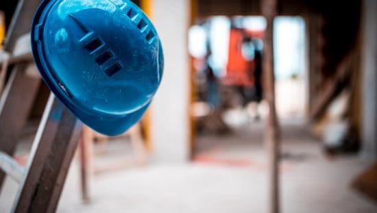 Guy who hangs up his blue hardhat on ladder could use some serious construction safety tips.
