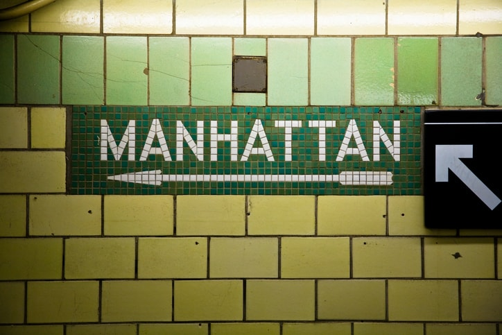New York City subway station showing which direction is Manhattan, where you can find the rats from commensalism.