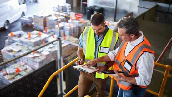Two warehouse managers reviewing ANSI standards and OSHA requirements for warehouse safety.
