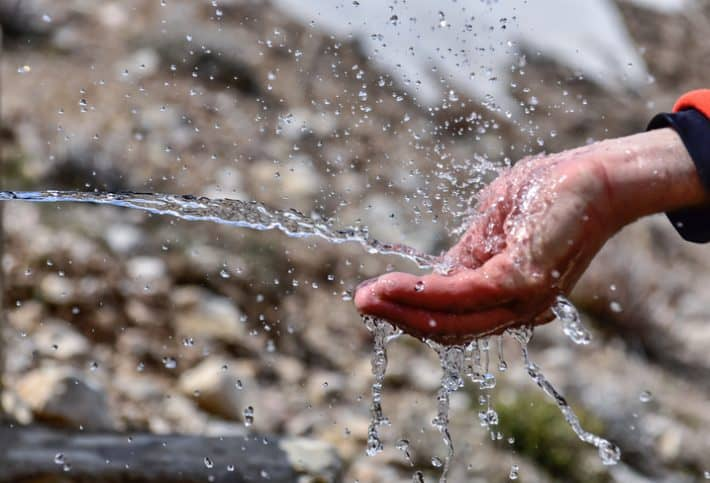 Clean drinking water spurting into cupped hands.