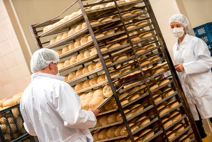 A suited up pair sorting bread safely while remembering ISO 22000:2018
