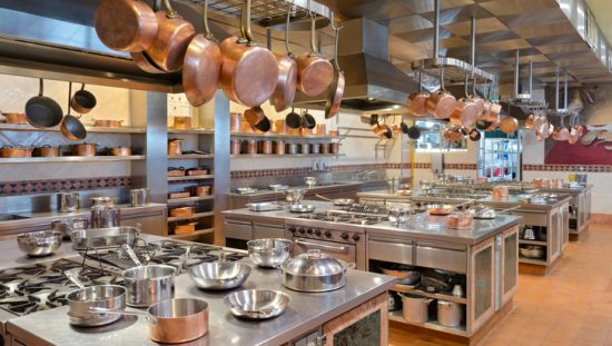 Copper pots and pans hanging in large restaurant NSF/ANSI 51-2019 kitchen.