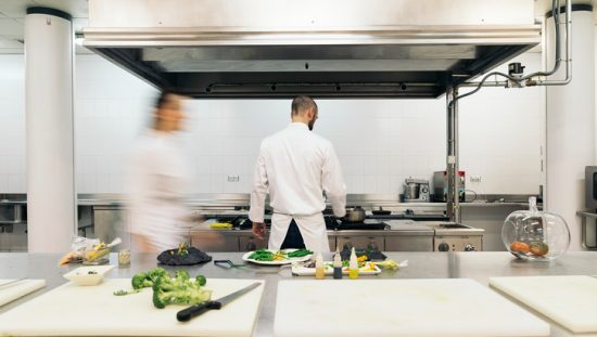 Chef hard at work fighting the dinner crowd under a kitchen exhaust system cleaned with ANSI/IKECA C10-2021.