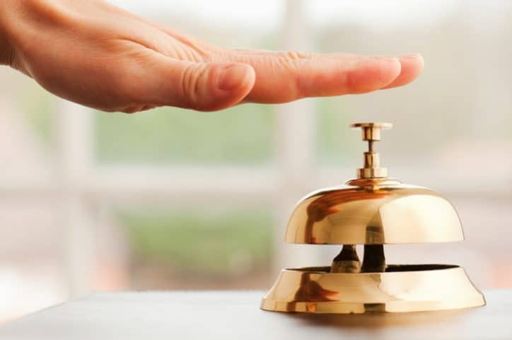 Hand tapping a gold bell for a customer complaint, which is handled with ISO 10002:2018