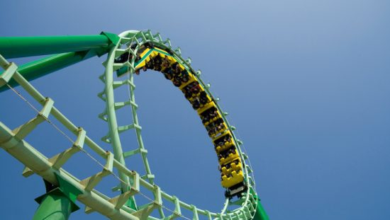 Green roller coaster loop providing ASTM F2291-20 amusement ride patrons with safe thrills.