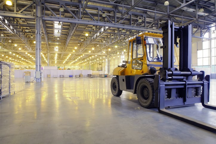 Bright yellow industrial low-lift truck ready for work in warehouse with ANSI/ITDSF B56.1 help.