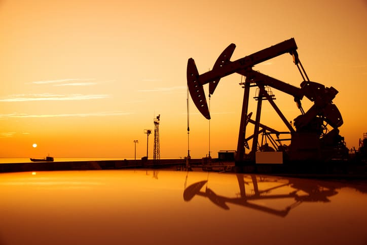 Oil pump jack the follows ASTM D4052 with the sunset in the background