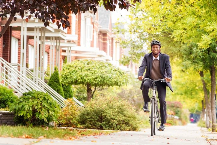 Man happily riding bike in lovely ISO 37120 sustainable community.