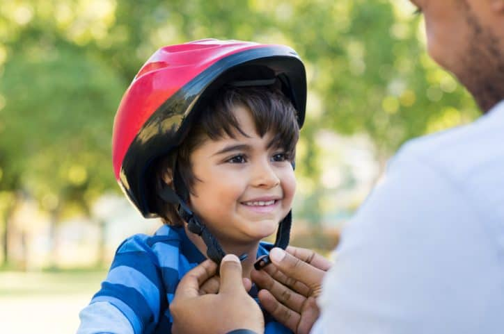 Father tightening red ASTM F1447-18 bicycle helmet on happy son's head.