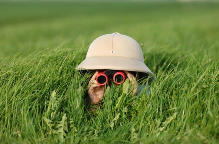 Boy pretending to be on a safari with binoculars in grass and wearing vintage pith helmet.