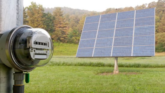 A solar PV panel in the grass connects to an electrical meter to measure energy management with ISO 50001:2018.