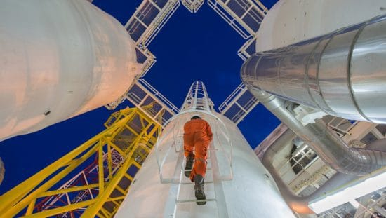 Worker in orange jumpsuit climbing to change power piping to ASME B31.1-2020.