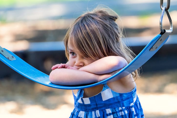 Girl looking sad on swingset, which can be prevented if designed with ASTM F1148-21