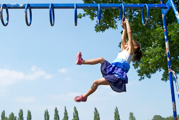 Girl hanging on blue home playground safety designed with ASTM F1148
