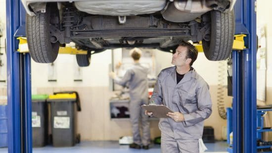 Auto mechanic in gray jumpsuit checking out car and depending on the AIAG CQI-20:2018 Problem Solving Guideline.