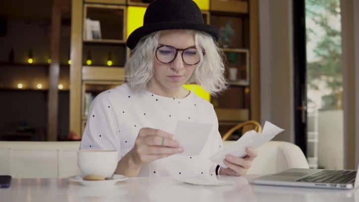 Hipster young woman checking her check and converting to Image Replacement Document (IRD).