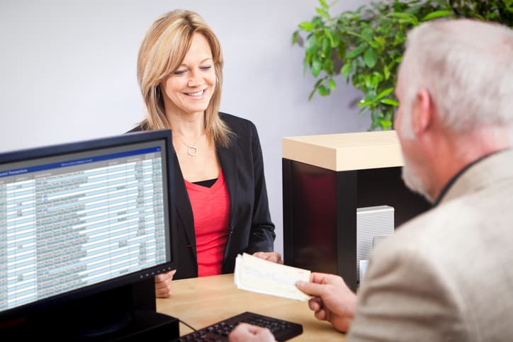 Businesswoman handing in a check to turn into an ANSI X9.100-140-2018 IRD.