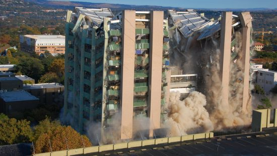 Building being demolished under ANSI/ASSP A10.7-2018 explosive blasting agents requirements.