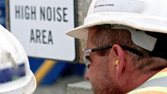 Construction manager with yellow earplugs blocking ASME PTC 36-2018 industrial noise.