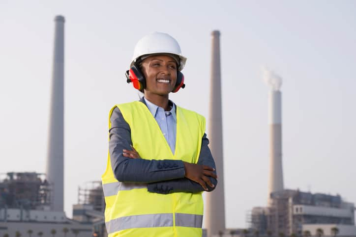 Woman working at energy plant prepared to follow ASME PTC 36-2018 to prevent industrial noise.