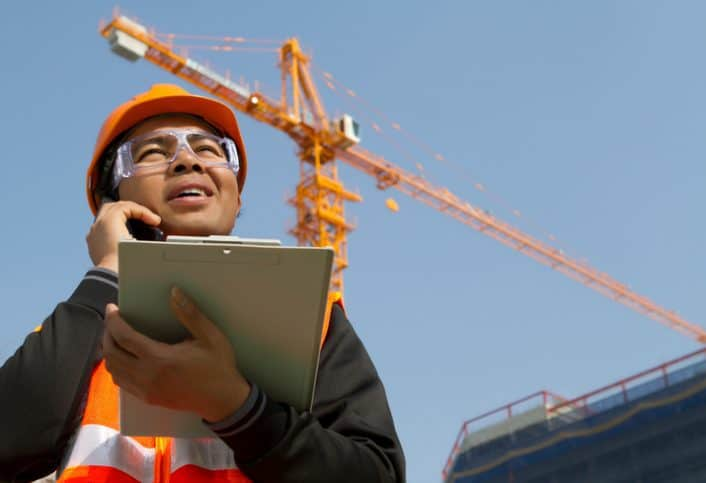 Construction site manager holding the ANSI/ASSP A10.28-2018 document and asking about work platforms suspended by cranes.